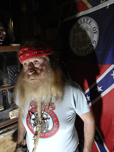 """Dent Myers is the proprietor of """"Wildman's Civil War Surplus and Herb Shop"""", a store in Kennesaw, Georgia which sells Civil War, KKK and Nazi memorabilia. He is famous for his beard, his friendly demeanor, his love of guns and his racism."""