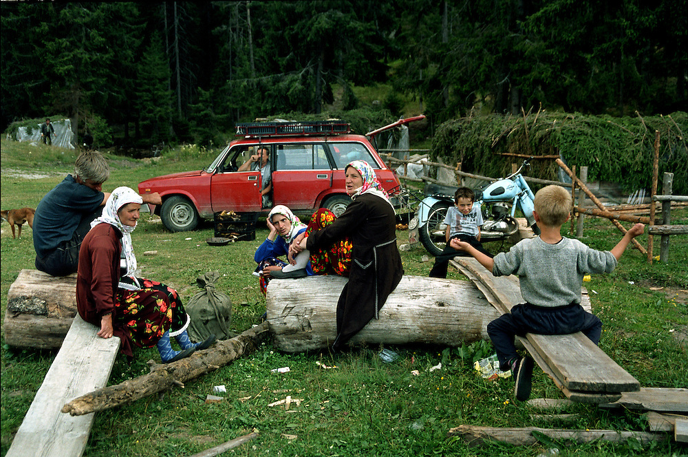 A group of people rest and after spending the day blueberry picking in the mountains. They have just sold their taking to a local middleman in the red car.