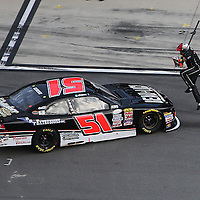 A pit crew member avoids the spun car of Jeremy Clements (51) during the Alert Today Florida 300 XFinity Series race at Daytona International Speedway on Saturday, February 21, 2015 in Daytona Beach, Florida.  (AP Photo/Alex Menendez)