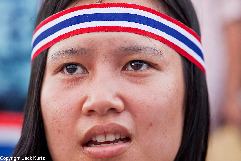 "Apr. 18, 2010 - Bangkok, Thailand: A woman with a Thai flag head band sings the Thai national anthem at the end of a Pink Shirt peace rally in Bangkok Sunday. Thousands of so called ""Pink Shirts"" jammed the area around Victory Monument in Bangkok to show support the Thai Monarch, King Bhumibol Adulyadej, and against the Red Shirts, who are demonstrating just a few kilometres away in the Ratchaprasong area. The Pink Shirts claim to not support either of the other political factions who wear colors - the Red Shirts, who support deposed Prime Minister Thaksin Shinawatra and their opponents the Yellow Shirts, who are against Thaksin.   Photo By Jack Kurtz"