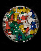 colorful pushpins in round container on a black background