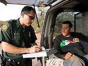 05 OCTOBER 2005 - DOUGLAS, AZ: US Border Patrol Agent JORGE REYNOSA, left, completes paperwork with JUAN PABLO PEREZ FERREIRA, after Ferreira was apprehended by the Border Patrol in the desert east of Douglas, AZ. Ferreira said he was originally from Mexico City and was trying to get to Phoenix, AZ, where he had a job working as a house painter waiting for him. Apprehensions of illegal immigrants in the Douglas area are down significantly in the last 18 months. In 2003, the Border Patrol apprehended an average of 1,500 people a day in and around Douglas. In September and October 2005 they are apprehending only about 150 - 200 people a day.  PHOTO BY JACK KURTZ