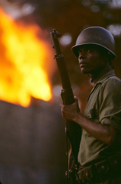 Haiti, Port-au-Prince, Soldier stands guard by burning house during political violence leading up to 1987 Presidential elections