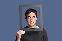Young man making funny faces through frame over blue background