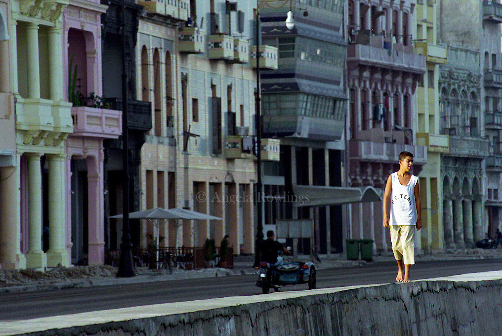 A boy walks barefoot along the Malécon in Havana.