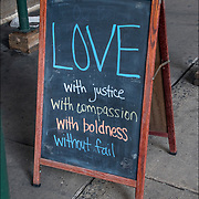 Blackboard sign outside of church &quot;LOVE with justice, with compassion, with boldness and without fail&quot;. <br />