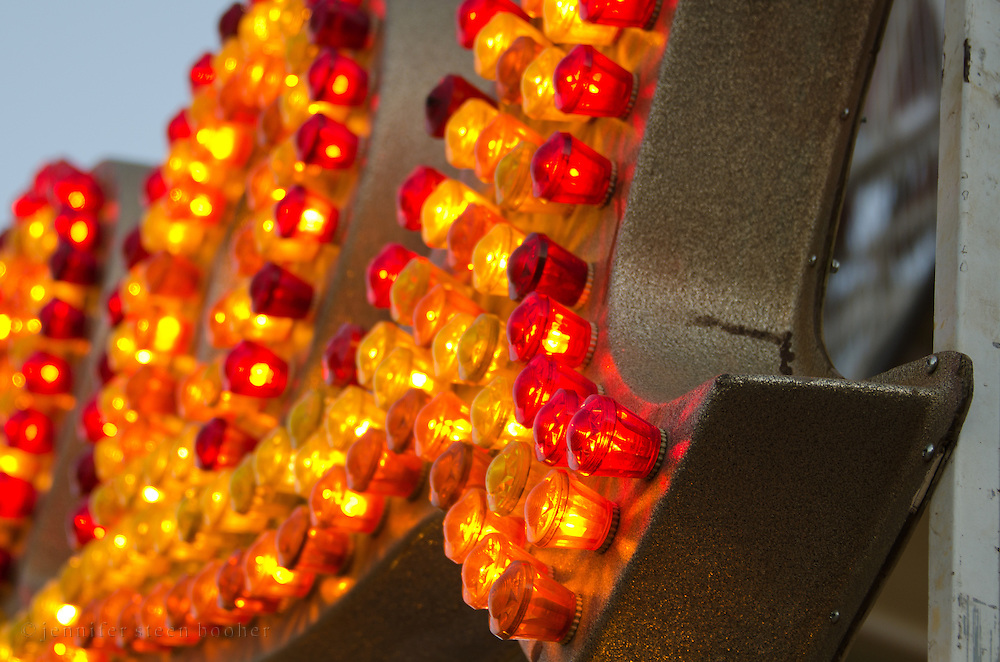Closeup view of a fairground ride sign with red and yellow light bulbs