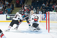 KELOWNA, CANADA - OCTOBER 22: Myles Bell #29 of the Kelowna Rockets is checked by Kenton Helgesen #3 of the Calgary Hitmen in front of Hitmen goalie #33 Chris Driedger on October 22, 2013 at Prospera Place in Kelowna, British Columbia, Canada.   (Photo by Marissa Baecker/Shoot the Breeze)  ***  Local Caption  ***