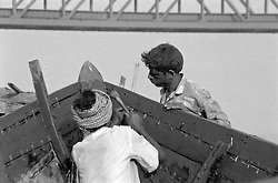 India, Varanasi, 1999. One to back the plank against the hammer's blow, the other to strike home a handmade tarred nail, these Varanasi boat builders are experts.