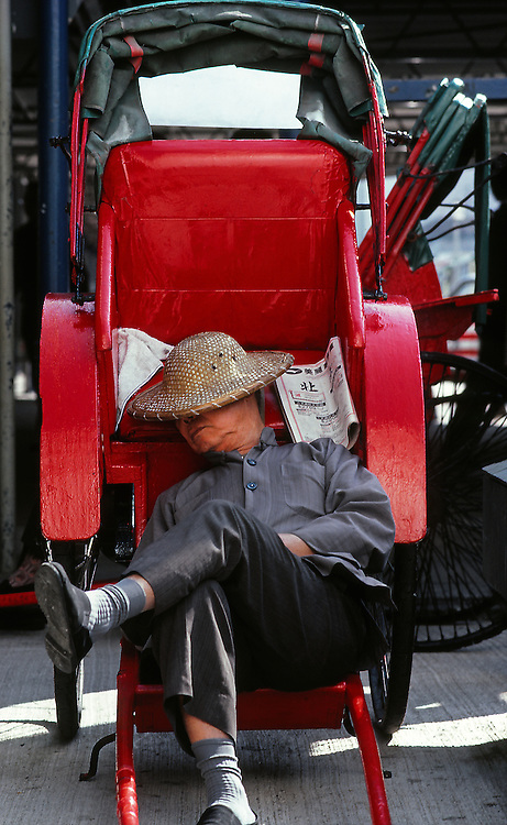 Rickshawman on rest, Hong Kong.