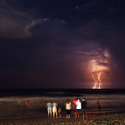 People play on Wrightsville Beach at night while lightning strikes over the ocean.