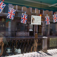 VENICE, ITALY - APRIL 29: Reflections of a canal over a British tourist that has some tea in a tea room which displays British flags and royal wedding memorabilia during the royal wedding on April 29, 2011 in Venice, Italy. The wedding of Britain's Prince William and Kate Middleton took place at Westminster Abbey in London. (Photo by Marco Secchi/Getty Images)