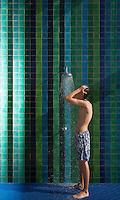 Teenage boy (16-17) standing under outdoor shower side view