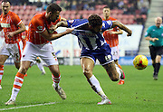 Wigan Striker Craig Davies and Blackpool Defender Clark Robertson battle during the Sky Bet League 1 match between Wigan Athletic and Blackpool at the DW Stadium, Wigan, England on 12 December 2015. Photo by Pete Burns.