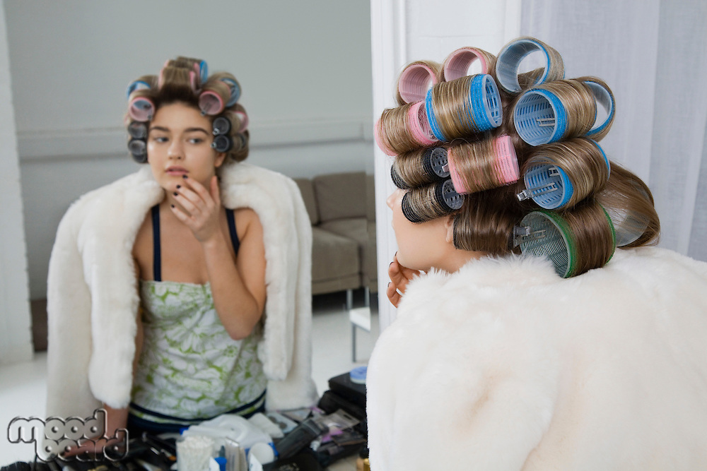 Model in Hair Curlers Looking at Reflection