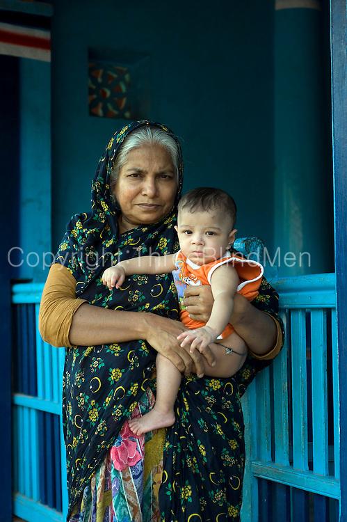 Grandmother and grandson on veranda of their home. Thittacheri.