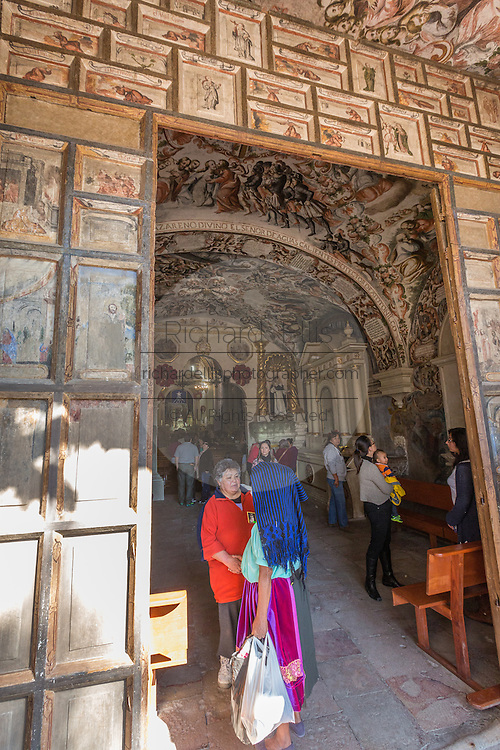 Pilgrims stand at the entrance to the Sanctuary of Atotonilco with Mexican folk Baroque murals painted on the ceiling and walls in Atotonilco, Mexico. The paintings were done by Antonio Martinez de Pocasangre and Jose Maria Barajas over a period of thirty years and is known as the Sistine Chapel of Mexico.