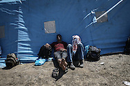 Gevgelija, Macedonia - Refugees and migrants resting under a tent at a temporary train station near the town of Gevgelija as they are waiting for the train to take them to the Macedonian - Serbian border, on the 23rd of August 2015. Thousands of refugees (mostly coming from Syria) and immigrants try every day to cross the Greek border to Macedonia (Fyrom), hoping to continue their journey to Central/North Europe and eventualy reach countries like Germany, Great Britain and Sweden.