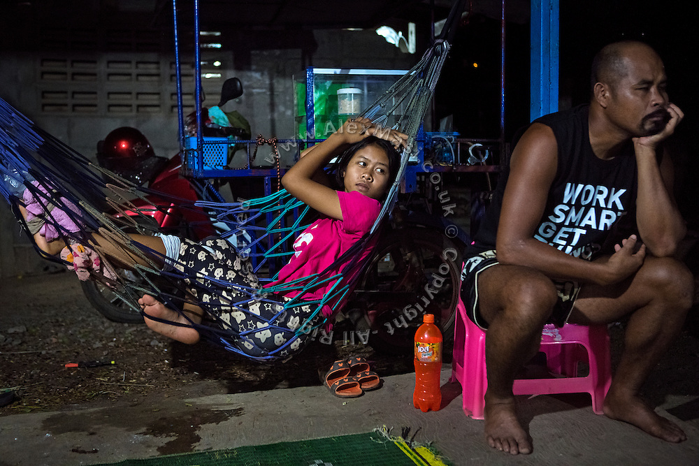 Next to her instructor Wichai Saengkeaw, 42, Phatsorn Bunmasen, 14, has injured her left foot during training, and she is relaxing on a hammock while watching television in her front yard, in a village near Ubon Ratchathani, northeast Thailand.
