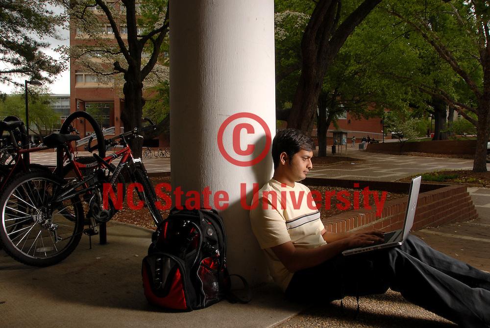 CALS major Kartik Joshi works on his laptop sitting under Harrelson Hall. PHOTO BY ROGER WINSTEAD