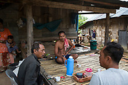 Supot Kalasong, 42, sits and chats with other villagers outside his house in the village after he was shot in April 2016.<br /> <br /> Since 2008, this community of around 70 families have been embroiled in a conflict with a palm oil company that locals allege has been trying to violently evict them. Since 2010, four members of the community have been shot dead and a fifth shot, but survived.<br /> <br /> For decades the palm oil company Jiew Kang Jue Pattana Co., Ltd has illegally occupied and cultivated palm oil trees on a 535-acre plot of land in the Chai Buri District of Surat Thani Province. <br /> <br /> The company operated with no official legal documentation or land concession, until the Southern Peasant's Federation of Thailand (SPFT), who supports the community, began investigating them and collecting evidence.<br /> <br /> This evidence ultimately lead to a Supreme Court ruling against the company for illegal trespassing and land encroachment. But the community still struggles to remain on the land to this day with the last shooting happening in April 2016, years after the court case was won.