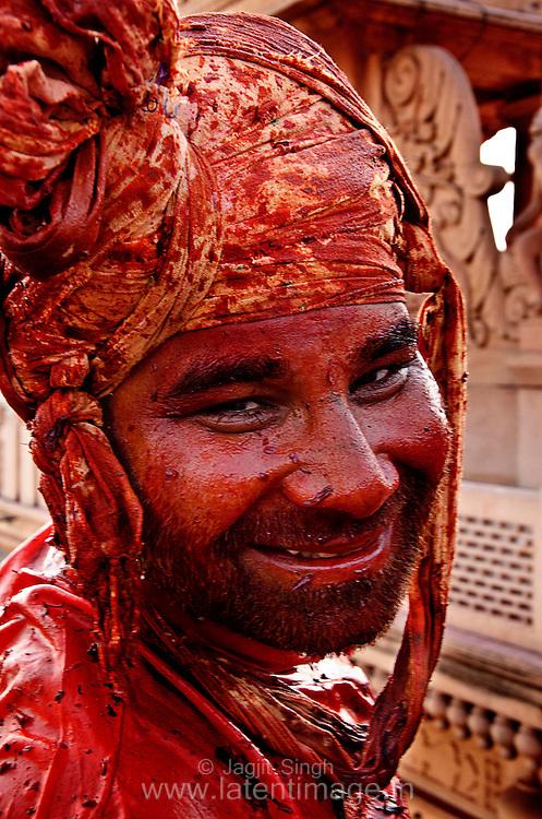 Drenched with water color, a man from Nandgaon at Radha Rani  temple, Barsana. Braj ki Holi