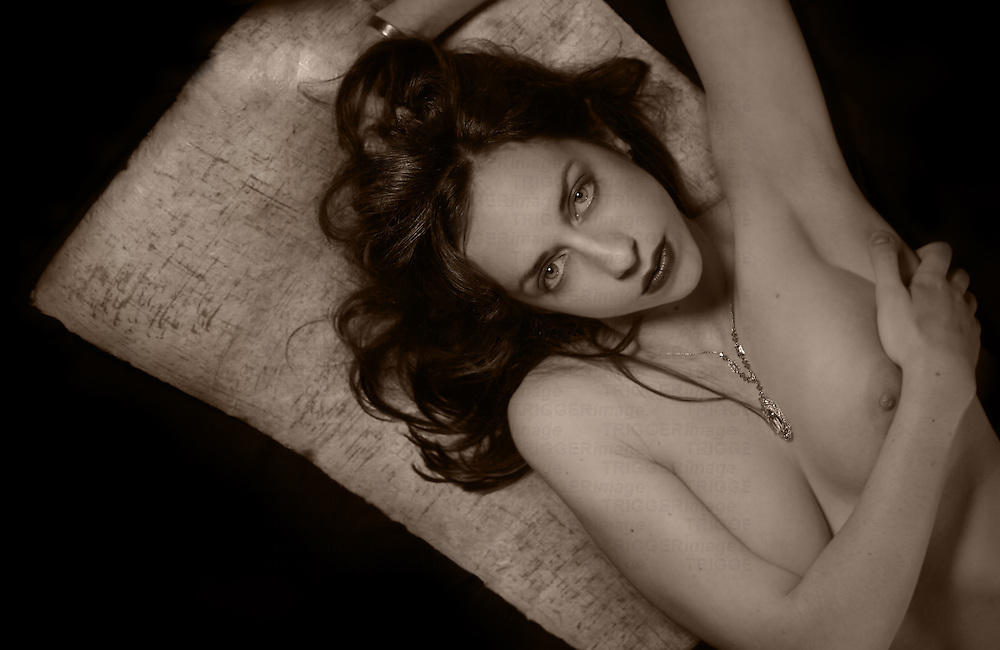 A beautiful woman lying naked on a cushion wearing a necklace.
