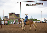 Cowboy riding on the back of horse at rodeo.