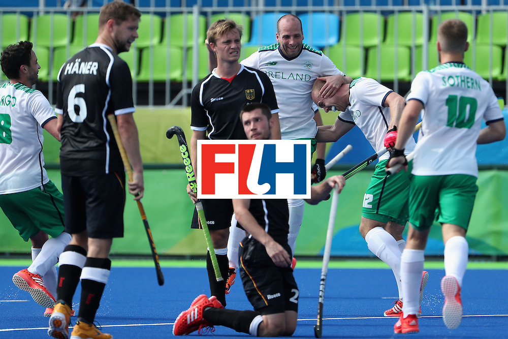 RIO DE JANEIRO, BRAZIL - AUGUST 09:  Eugene Magee #12 (second from right) of Ireland is congratulated by Peter Caruth #13 and Alan Sothern #10 after scoring a goal against Germany during the hockey game on Day 4 of the Rio 2016 Olympic Games at the Olympic Hockey Centre on August 9, 2016 in Rio de Janeiro, Brazil.  (Photo by Christian Petersen/Getty Images)