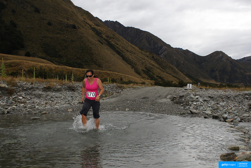 Runner Michelle Bose crosses  Moke Creek on the Ben Lomond High Country Station during the Pure South Shotover Moonlight Mountain Marathon and trail runs. Moke Lake, Queenstown, New Zealand. 4th February 2012. Photo Tim Clayton