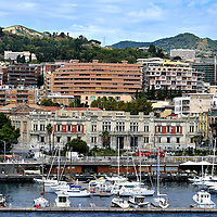 """Cityscape and History of Messina, Italy<br /> When Messina was founded during the 8th century BC, it was called Zancle after its first king, Zanclus. According to mythology, he and the giant Orion built the city. Since then, Messina has been ruled by several nationalities including the Greeks, Romans, Goths, Byzantines, Arabs, Normans and Spanish. The street along the small boat quay is Via Vittorio Emanuele II. It honors the first leader of the Kingdom of Italy from 1861 until 1878. The namesake for the parallel road is Giuseppe Garibaldi.  He is called the """"father of the fatherland"""" for his military role in unifying Italy during the mid-19th century. Seen here in the Piazza Unification of Italy is the Palace of the Prefecture. Despite being ravished by wars, earthquakes and tsunamis plus the Black Death plague, Messina has prospered as the """"Doorway to Sicily."""""""