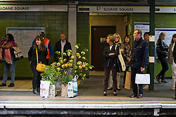 © London News Pictures. 23/05/2015. London, UK. People wait with their flower purchases to board a train at Sloan Square tube station. Members of the public carry exhibitors' plants from the 2015 Chelsea Flower show, which ends today (Sat). The Royal Horticultural Society flagship flower show has been held at the Royal Hospital in Chelsea since 1913. Photo credit: Ben Cawthra/LNP