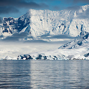 Steep ice-covered mountains line the shoreline of Fournier Bay on the western coast of the Antarctic Peninsula.