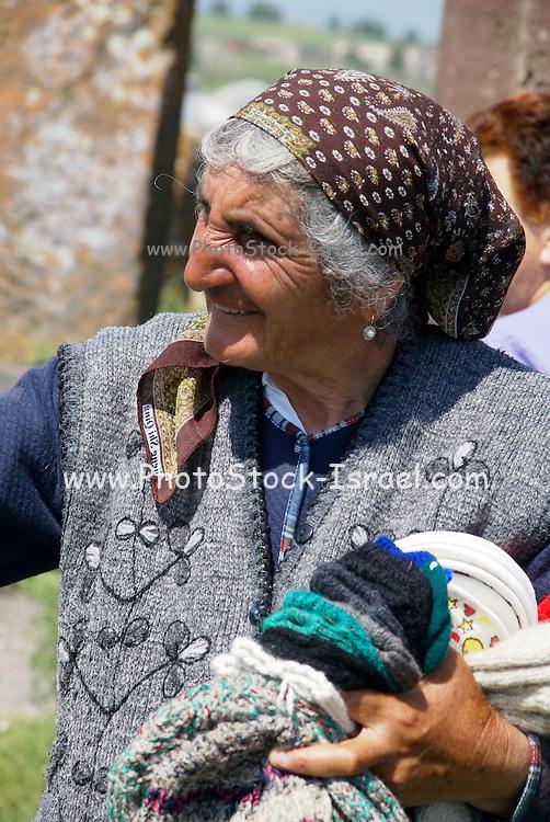 Armenia, Lake Sevan, Noraduz cemetery Local woman sells souvenirs to tourists