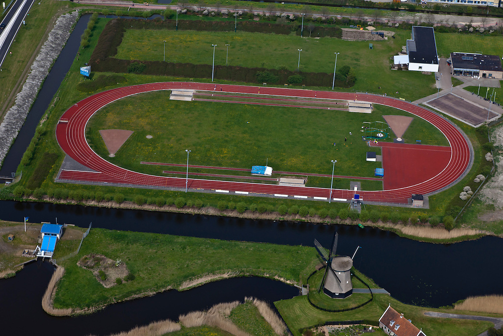 Nederland, Noord-Holland, Alkmaar, 28-04-2010; atletiekbaan en poldermolen De Viaan. Samen met een elektrisch gemaal (li) zorgt de molen voor de waterhuishouding in de Bergermeerpolder..The track and windmill Viaan. Together with the electric pumping station (left) the mill manages the waterlevels in the polder.luchtfoto (toeslag), aerial photo (additional fee required).foto/photo Siebe Swartp
