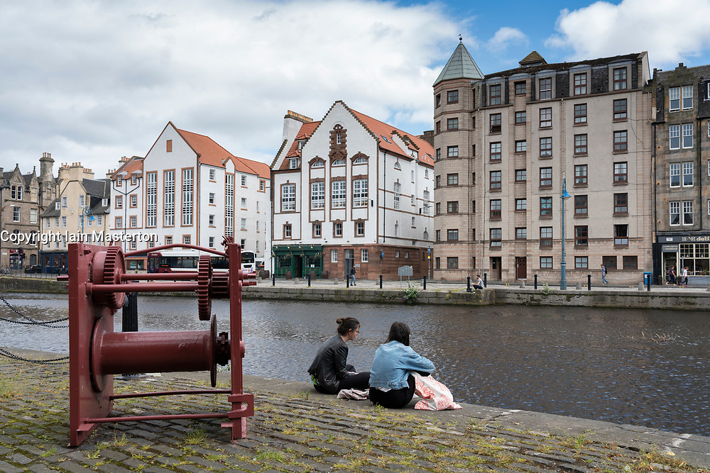 Couple sitting beside Water of Leith river in Leith , Scotland, UK