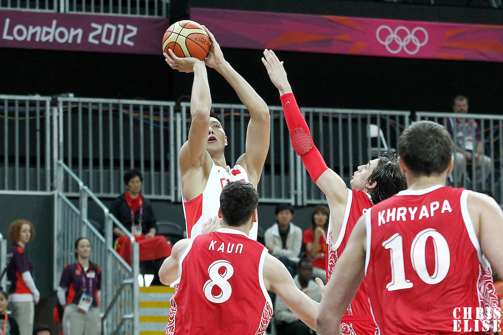 31 July 2012: China Jianlian Yi takes a jumpshot over Russia Alexey Shved during the 73-54 Russia victory over China, during the men's basketball preliminary, at the Basketball Arena, in London, Great Britain.