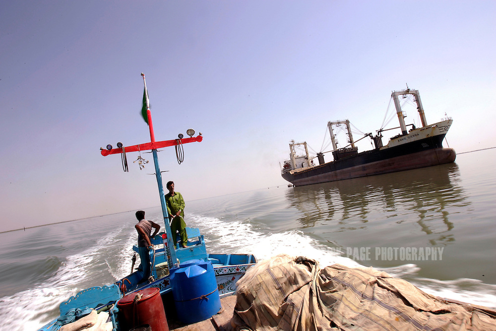 KARACHI, PAKISTAN - MARCH 1: A fishing boat passes an international cargo vessel off the coast of Karachi, March 1, 2007, Karachi, Pakistan. Hundreds of local fishing communities in Pakistan are suffering hardship due to the presence of deep-sea trawlers from the Far East. The Pakistani government's policy of opening up its waters to transnational fleets and the liberalisation of the global fishing trade are depleting stocks and forcing local residents out of their traditional livelihoods. (Photo by Warrick Page)