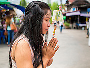 11 JULY 2014 - BANGKOK, THAILAND: A Thai woman prays at Wat Mahabut for Asalha Puja Day. Asalha Puja is the day the Lord Buddha preached his first sermon to followers after attaining enlightenment. The day is usually celebrated by merit making and listening to a monks' sermons. It is also day before the start of the Rains Retreat, the three month period when monks stay in their temple for intense mediation and spiritual renewal.    PHOTO BY JACK KURTZ