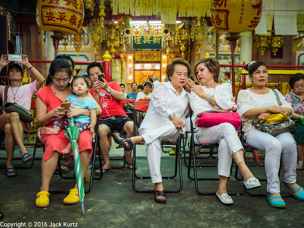 04 OCTOBER 2016 - BANGKOK, THAILAND:  People watch the Chinese opera at the Vegetarian Festival at the Chit Sia Ma Chinese shrine in Bangkok. The Vegetarian Festival is celebrated throughout Thailand. It is the Thai version of the The Nine Emperor Gods Festival, a nine-day Taoist celebration beginning on the eve of 9th lunar month of the Chinese calendar. During a period of nine days, those who are participating in the festival dress all in white and abstain from eating meat, poultry, seafood, and dairy products. Vendors and proprietors of restaurants indicate that vegetarian food is for sale by putting a yellow flag out with Thai characters for meatless written on it in red.    PHOTO BY JACK KURTZ