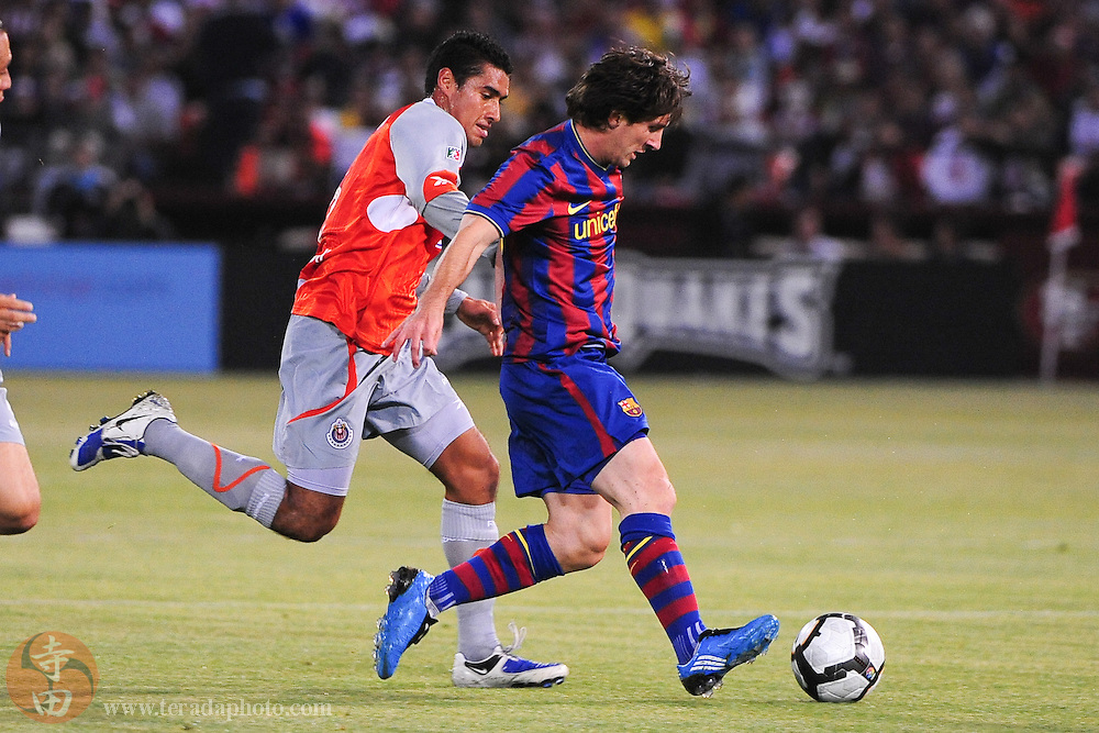 August 8, 2009; San Francisco, CA, USA; FC Barcelona forward Lionel Messi (10, right) controls the ball against Chivas de Guadalajara midfielder Patricio Araujo (5, left) during the first half in the Night of Champions international friendly contest at Candlestick Park.