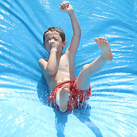 Kaden Throckmorton, 6, slides down one of many inflatabes at Guntown's 8th annual Fourth of July celebration Saturday