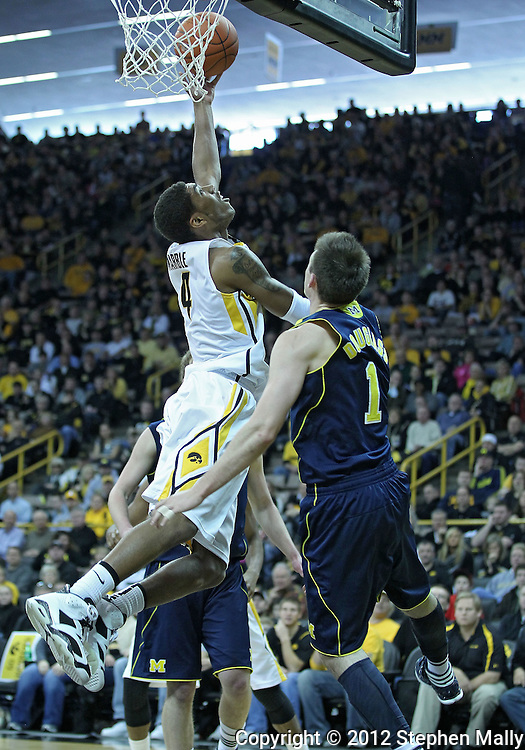 January 14, 2011: Iowa Hawkeyes guard/forward Roy Devyn Marble (4) puts up a shot around Michigan Wolverines guard Stu Douglass (1) during the NCAA basketball game between the Michigan Wolverines and the Iowa Hawkeyes at Carver-Hawkeye Arena in Iowa City, Iowa on Saturday, January 14, 2011. Iowa defeated Michigan 75-59.