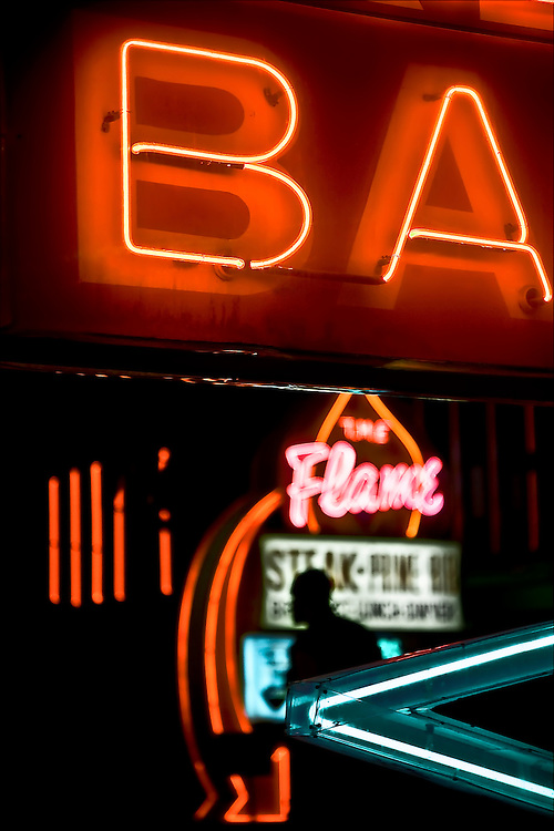 Dark figure walks briskly under bar sign at night in Las Vegas, NV.  Copyright 2008 Reid McNally.