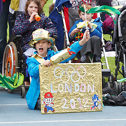 © Licensed to London News Pictures.  09/07/2012. STOKE MANDEVILLE, UK. Local school children wait for the the Olympic Torch in Stoke Mandeville Stadium, birthplace of the Paraolympics on Day 52 of the Relay through Britain. Photo credit: Cliff Hide/LNP