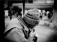 Homeless man nibbles on a chocolate bar on the grounds of Senso-ji Temple where homeless men regularly congregate, Asakusa, Tokyo, Japan.