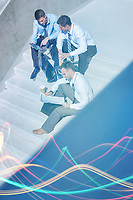 Group of handsome businessman sitting on stairs while preparing business plans during break