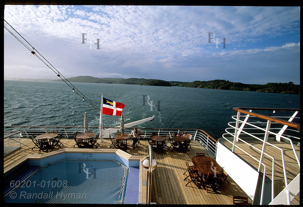 Lone passenger sits by pool of cruise ship Clipper Odyssey watching scenery along north shore of Stewart Island; New Zealand.