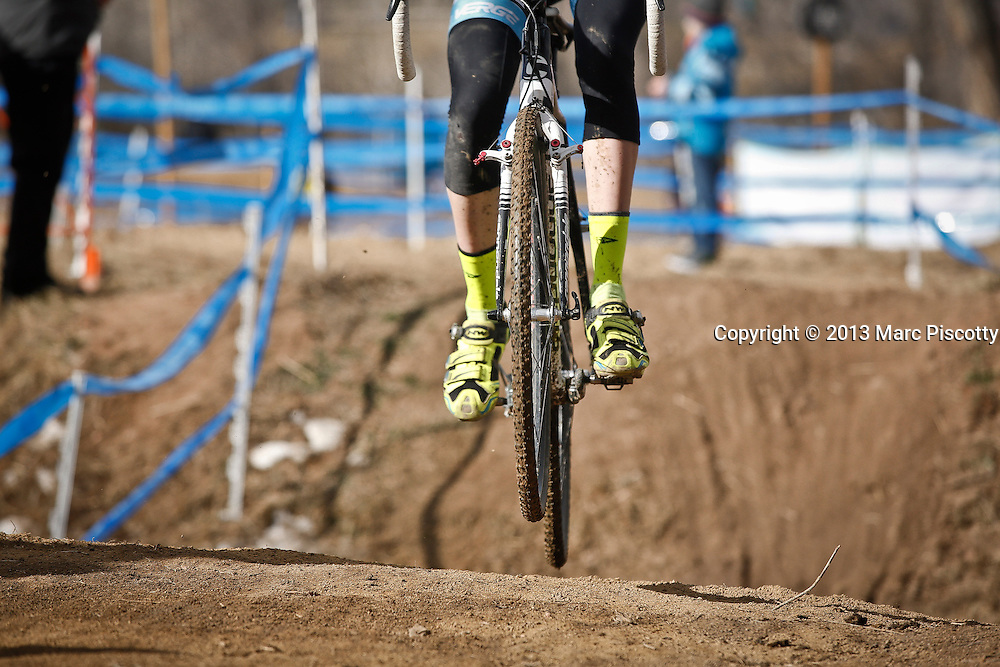 SHOT 1/12/14 12:48:31 PM - A Men's Junior 17-18 racer's tires leave the ground after a gulley crossing at the 2014 USA Cycling Cyclo-Cross National Championships at Valmont Bike Park in Boulder, Co.  (Photo by Marc Piscotty / © 2014)