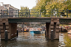 Total canal scene -- tour boat, houseboats, bikes, and architecture.
